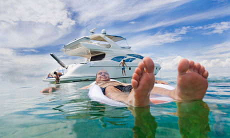 A man swimming off his luxury yacht